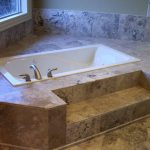 beige granite white bathtub surrounded with beige granite