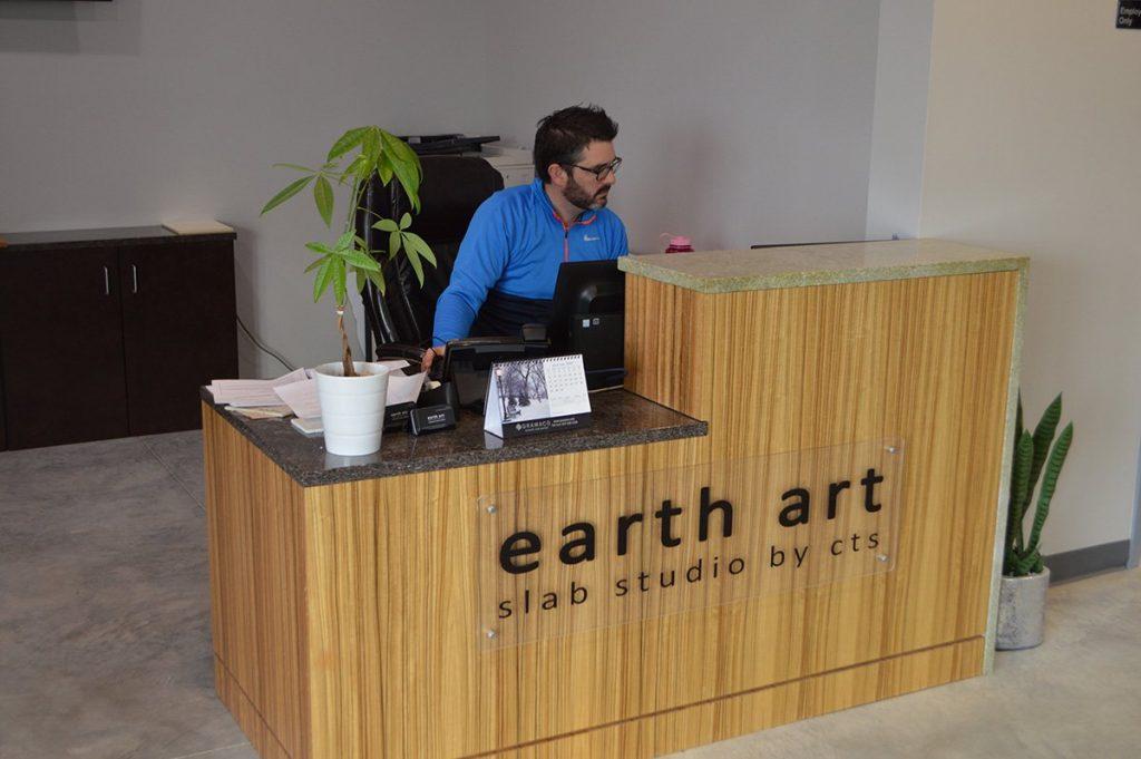 man at front desk at earth art